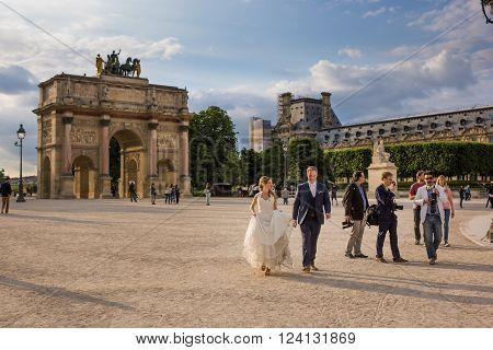 Paris, France May 26 2015: Photographers with bride and groom near the Louvre and Arc de Triomphe in Paris