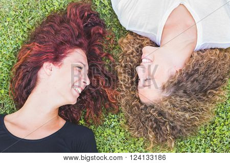Two Girls Lying On The Grass And Looking Each Other