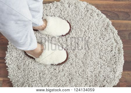Woman staying in white slippers on gray carpet