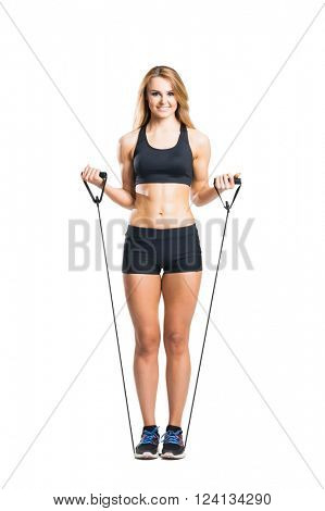Fit, healthy and sporty woman in sportswear doing expander exercise  isolated on white.
