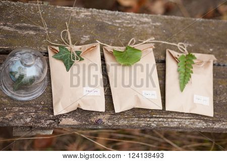 Three brown craft gift boxes decorated with fern and ivy leaves with glass box on wooden background ** Note: Soft Focus at 100%, best at smaller sizes