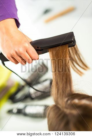 Close-up of a hairdresser straightening long blonde hair with hair irons.