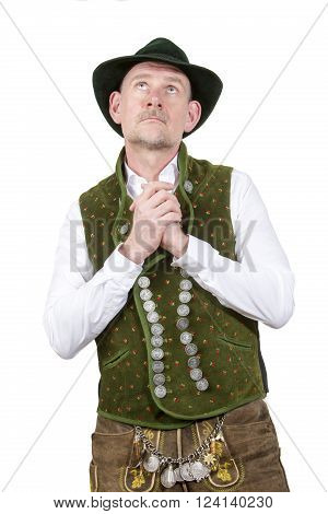 portrait of bavarian man wearing traditional bavarian clothes praying and looking up