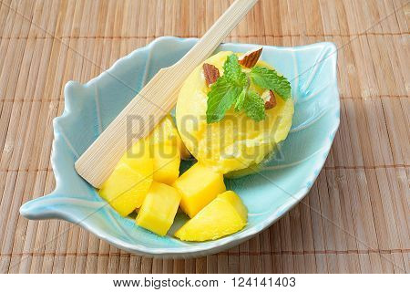 Scoop of homemade mango ice cream with fresh mangos