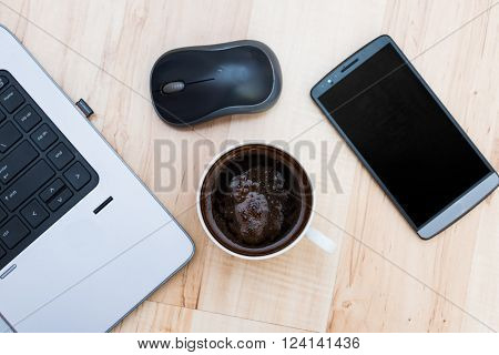 laptop, smartphone, mouse and coffee on a wooden floor