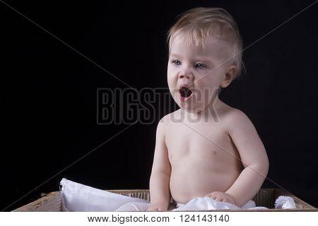 One year old boy is yawning black background