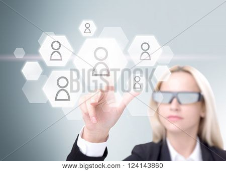Businesswoman in 3D glasses touching virtual screen hexagonals with people models on it. Grey background. Concept of 3D glasses.