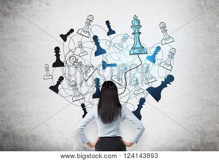 Businesswoman with hands on hips back view chess figures drawn on concrete wall behind blue queen. Concept of game.