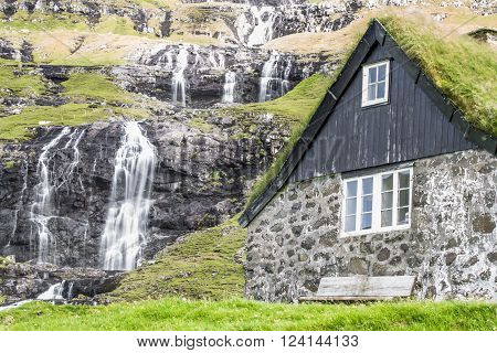 Old farmhouse with traditional turf roof . Saksun is a village surrounded by high mountains near the north-west coast of the Faroese island of Streymoy.