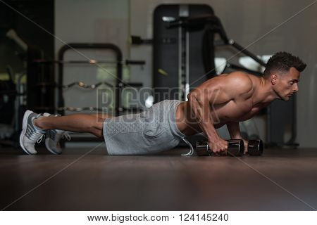 Young Man Doing Push Ups With Dumbbells On Floor