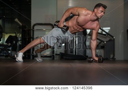 Bodybuilder Doing Push Ups With Dumbbells On Floor