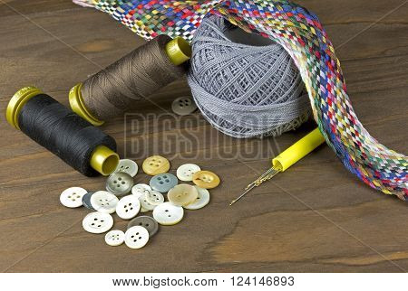 A collection of sewing tools and supplies isolated on a wooden background. ** Note: Soft Focus at 100%, best at smaller sizes