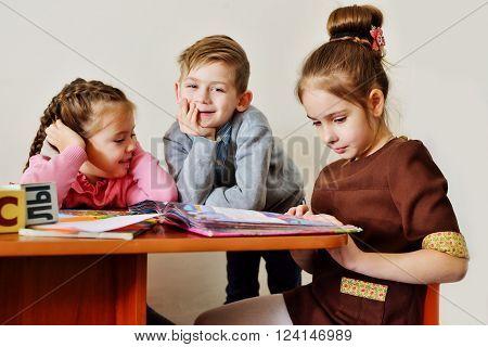 three happy children are in the kindergarten