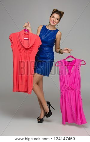 Beautiful happy woman holding  two dresses on hangers. Price tags. Over grey background. Copy space.