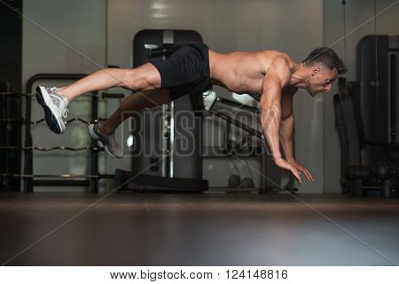 Young Man Doing Extreme Push Ups On Floor
