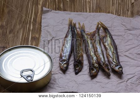 Smoked capelin and conserve tins on brown  wooden background