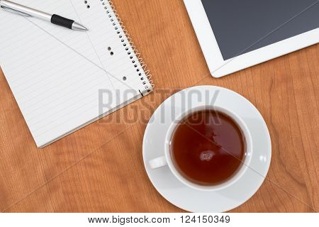 Tablet Pc And Notepad And A Cup Of Tea On Wooden Table From Abov