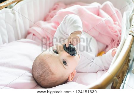 newborn pink cradle hold black pacifier hand ** Note: Soft Focus at 100%, best at smaller sizes