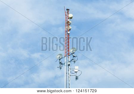 White and red color antenna repeater tower on blue sky telecommunication concept