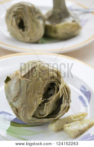 steamed artichokes in a white dish in foreground with on the background a blurry artichoke