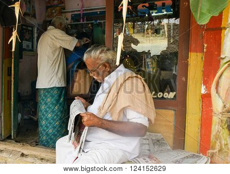 Thanjavur India - October 15 2013: Older man reads the newspaper while waiting his turn at the barber shop in the morning.