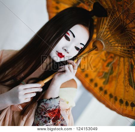 Girl in the Japanese style geisha with umbrella