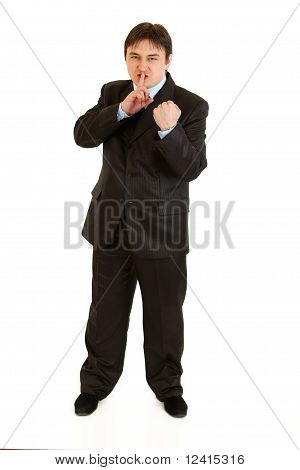 Angry businessman with finger at mouth and threaten with fist isolated on white