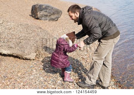 Father and daughter playing on a riverbank in spring time