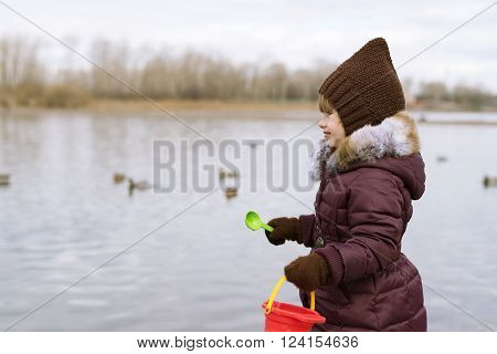 Profile portrait of a little girl standing on riverbank with plastic spoon and red bucket in spring time