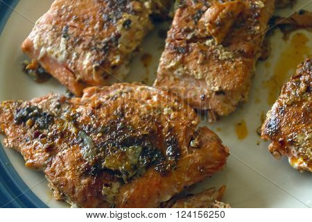 Close up of a plate of healthy salmon cooked with herbs and extra virgin olive oil