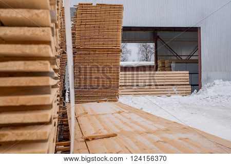 At sawmill. Image of boards stacked outside in winter time