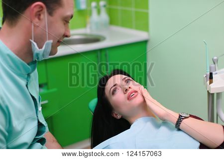 people medicine stomatology and health care concept - woman patient talking to male dentist and complain of toothache at dental clinic office