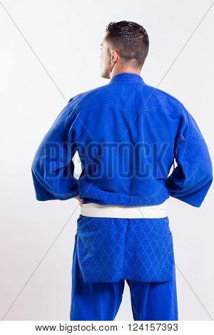 karate teacher back with blue kimono on gray background