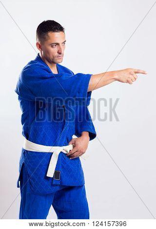 karate teacher with blue kimono on gray background