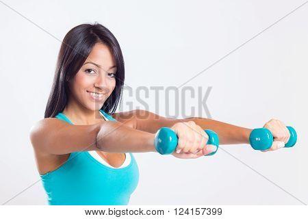 beautiful woman lifting weight locking at camera