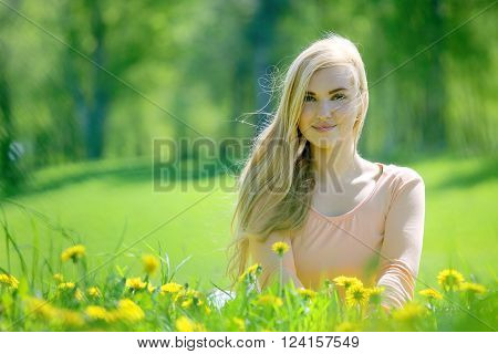 Beautiful young woman laying in spring park with dandelion flowers