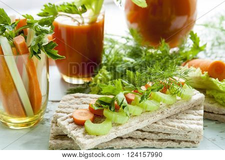 Plain rye cakes galette rye with fresh carrots celery and parsley around fresh carrot juice fresh carrot and celery on light background