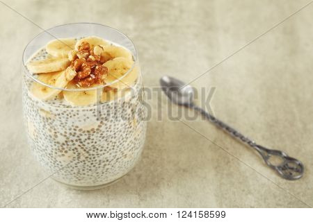 Chia seeds pudding with banana and hazelnut on grey textured background