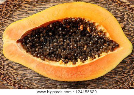 Halved papaya on a wooden plate