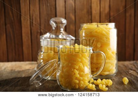 Raw pasta in glassware on wooden background