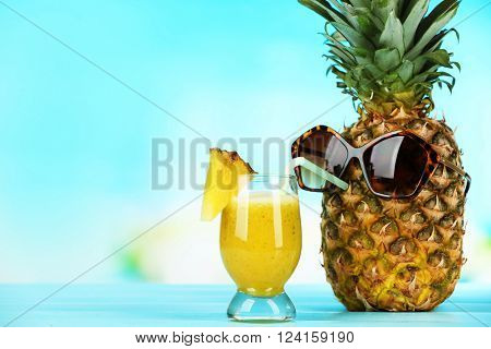 Ripe juicy pineapple in sun glasses drinking smoothie from glass on blue blurred background