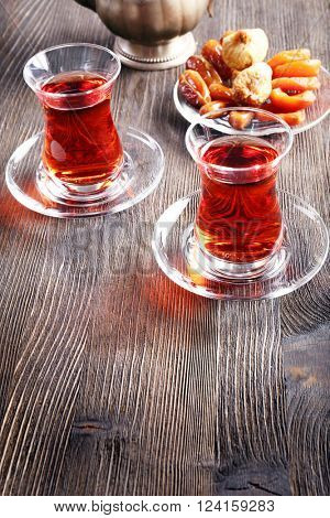 Black brewed tea in glass cups with eastern sweets on wooden table