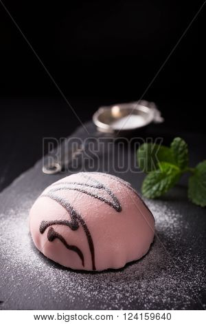 Individual mousse cake in the form of hemisphere covered with pink glaze with mint leaves on dark background. Holiday food concept with copy space for text.