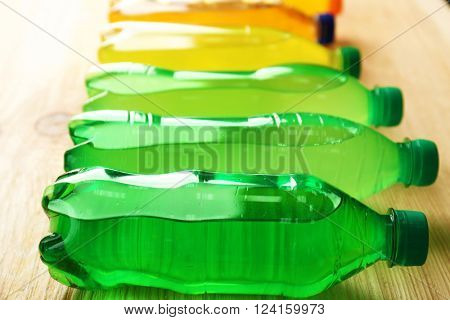Soft drinks bottles on the wooden table, close up