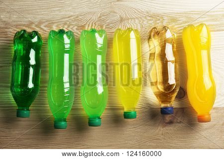 Soft drinks bottles on the wooden table, top view