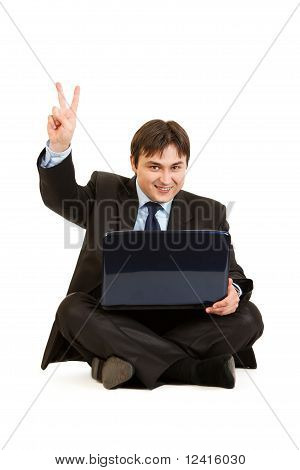 Smiling businessman sitting on floor with laptops and showing victory gesture isolated on white