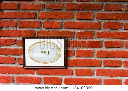 Framed number plate with 401 written on it, mounted on a brick wall. A great reference to the 401k retirement fund or unauthrized access in HTTP