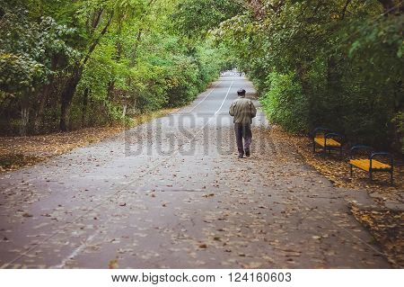 An elderly man is walking trough the park in the early morning. Early autumn. September. Odessa. Solitude. Yellow leaves on the road