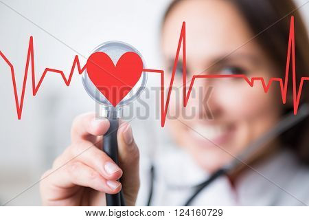 Doctor with phonendoscope at background heart and cardiogram in front. Concept of medical help.