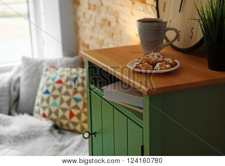 Biscuits and cup of tea on bedside table indoors